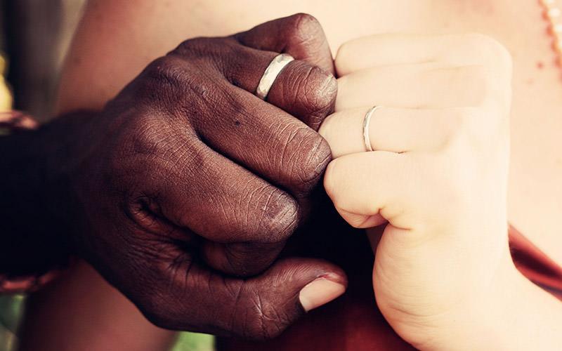 intercultural couple displaying their wedding rings